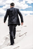 Man in formal wear rising up by desert dune — Stock Photo