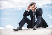 Frustrated businessman on top of sand dune — Stock Photo
