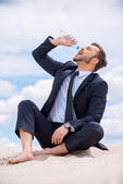 Businessman drinking water on top of sand dune — Stock Photo