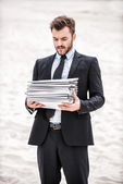 Businessman holding stack of paperwork — Photo
