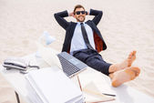 Man in formal wear and sunglasses holding his feet on table — Stock Photo