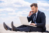 Man in formal wear working on laptop in desert — Stock Photo