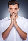 Man in white shirt  praying — Stock Photo