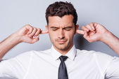 Man in shirt and tie holding fingers in ears — Stock Photo