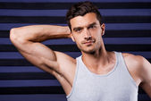 Man in tank top holding hand behind head — Stock Photo