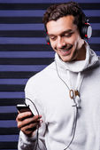Young man in headphones holding MP3 Player — Stock Photo
