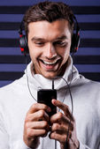 Man in headphones holding MP3 Player — Stock Photo