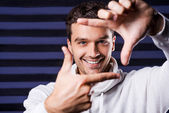 Man in white sweater gesturing finger frame — Stock Photo