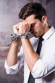 Frustrated young man trapped in chains — Stock Photo
