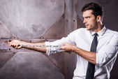 Man in shirt and tie stretching a chain — Stock Photo