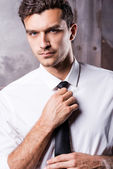 Man in formalwear adjusting his necktie — Stock Photo
