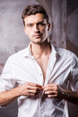 Handsome man buttoning shirt. — Stock Photo