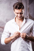 Man buttoning his white shirt — Stock Photo