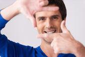 Man in blue sweater gesturing finger frame — Stockfoto