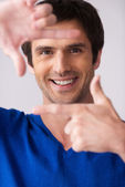 Man in blue sweater gesturing finger frame — Stock Photo