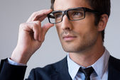Man in formalwear adjusting his glasses — Stock Photo