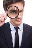 Man in formalwear examining you with magnifying glass — Stock Photo