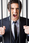 Man in formalwear standing behind a prison cell — Stock Photo