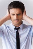 Man in shirt and tie covering ears — Stock Photo