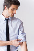 Man in shirt and tie adjusting his sleeve — Stock Photo