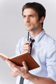 Man in formalwear holding note pad — Stock Photo