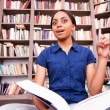 African female student holding a book and pointing up — Stock Photo #49280803