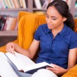African female student reading a book — Stockfoto