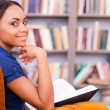 African female reading a book in library. — Stock fotografie #49280943