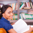 African female student sitting in library — Stok fotoğraf #49280945