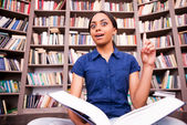 African female student holding a book and pointing up — Stock Photo