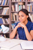 Black woman sitting at the library desk — Stock Photo