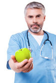 Surgeon in blue uniform stretching out apple — Stock Photo