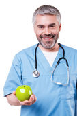 Surgeon in blue uniform holding apple — Stock Photo