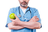 Surgeon in blue uniform holding green apple — Stock Photo