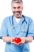 Cardiology surgeon holding heart shape toy n white — Stock Photo