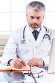 Mature grey hair doctor writing in note pad — Stock Photo