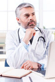 Thoughtful mature grey hair doctor — Stock Photo