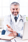 Doctor stretching out hand — Stock Photo