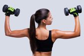 Sporty woman exercising with dumbbells — Stock Photo