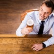 Man in shirt and tie examining glass with beer — Stock Photo #49601797