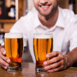 Bartender stretching out glasses with beer — Stock Photo #49602499