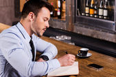 Man in shirt and tie writing in note pad — Stock Photo