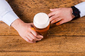 Hands holding beer glass — Stock Photo
