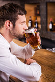 Man drinking beer in bar — Stock Photo