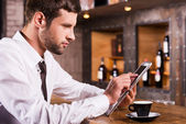 Man at the bar counter and working on tablet — Stock Photo