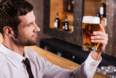 Man examining glass with beer — Stock Photo