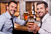 Men holding glasses with beer — Stock Photo