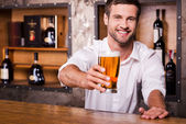 Bartender stretching out glass with beer — Stock Photo