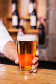 Man stretching out glass with beer — Stock Photo