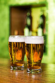 Glasses with beer at bar counter — Stock Photo